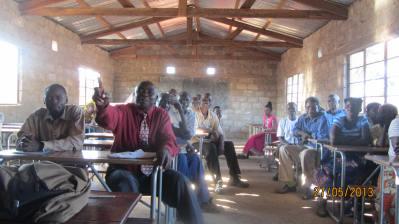 A teacher sits in a classroom where they teach four classes
